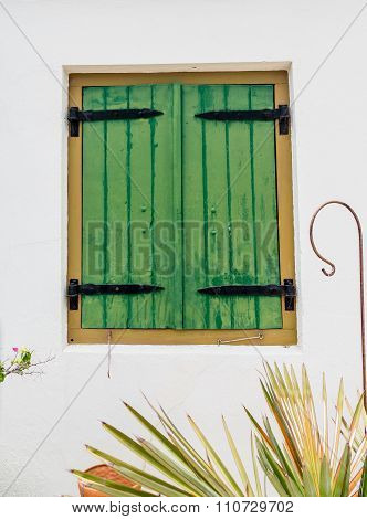 Green Wood Shutters With Black Iron Hinges