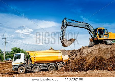 Industrial Truck Loader Excavator And Bulldozer Moving Earth And unloading in dumper trucks