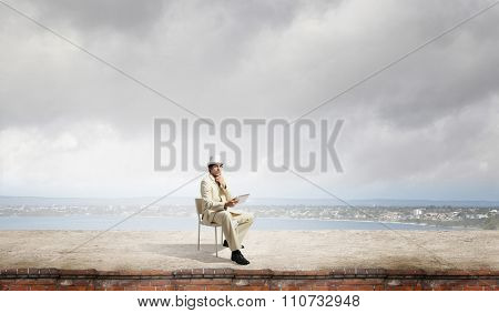 Young thoughtful businessman sitting in chair on top and using tablet