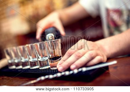 Bartender Pouring Brown Alcoholic Cocktail In Glasses On Bar
