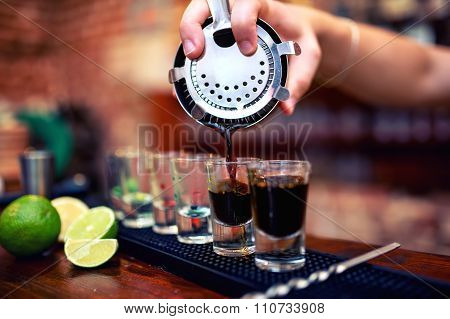 Barman Mixing And Pouring A Summer Alcoholic Cocktail Into Small shot glasses