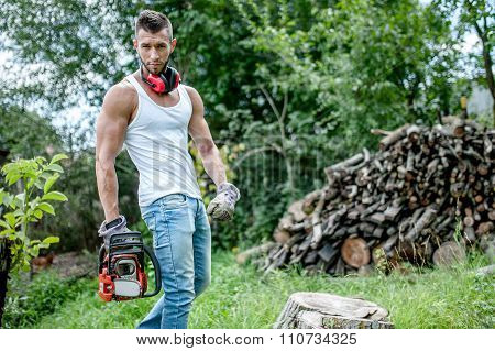 portrait of expressive muscular lumberjack man with chainsaw and tank top in forest