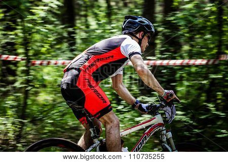 young man athlete cyclist rides through  forest. feet and hands in dirt