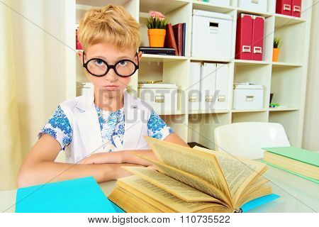 Smart boy wearing glasses sitting at the desk and seriously looking at the camera. Education.