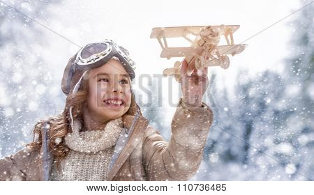happy child playing with toy plane outdoors in winter