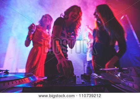 Girl adjusting deejay equipment at disco