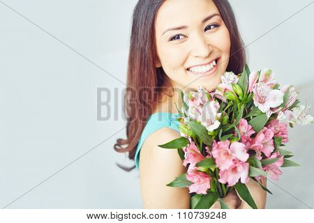 Smiling young woman holding floral bouquet