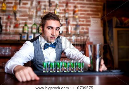 Portrait Of Young Male Barman Behind The Bar With Alcoholic Shots