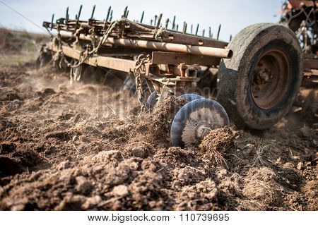 Close-up Of Tractor Working The Field By Plowing And Cultivating