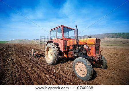 Farmer Working The Fields With Tractor And Plow