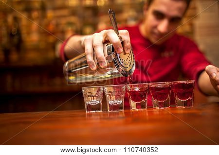 Barman With Cocktail Shaker Pouring Red Alcoholic Drink Into Glasses