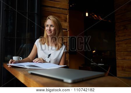 Hipster girl with good mood sitting with big notepad in coffee shop during her recreation time