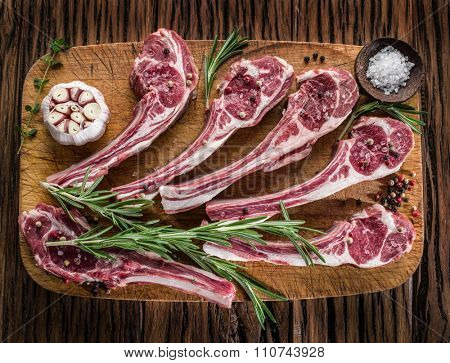 Raw lamb chops with garlic and herbs on the old wooden table.
