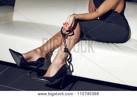 Sexy Woman Holding Handcuffs On Sofa