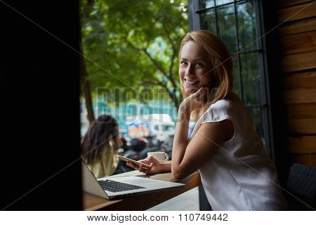 Young happy charming female posing while holding mobile phone
