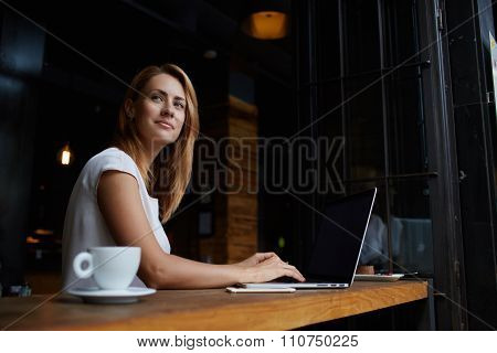 Young charming female freelancer thinking about new ideas during work on laptop computer