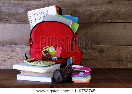 Backpack with school supplies on old wooden table