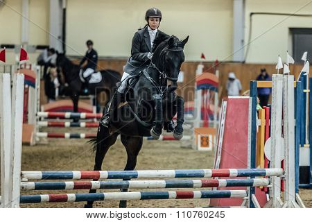 young woman rider horse overcomes obstacles sports complex indoors