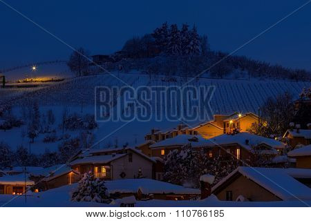 View of rural houses and hill covered with snow on background in evening in Piedmont, Northern Italy.