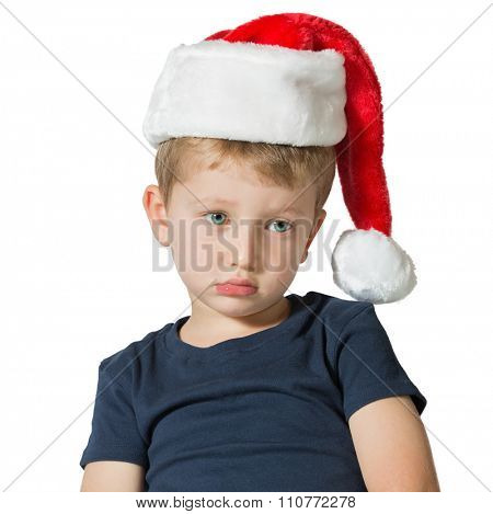 The child has sad blue eyes and fair soft hair. The charming little boy in red cap of Santa Claus. Photo executed on a white background