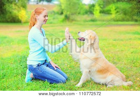 Happy Owner Woman Training Golden Retriever Dog On Grass In Park