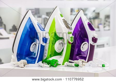 three colored electric irons at retail store shelf, defocused background