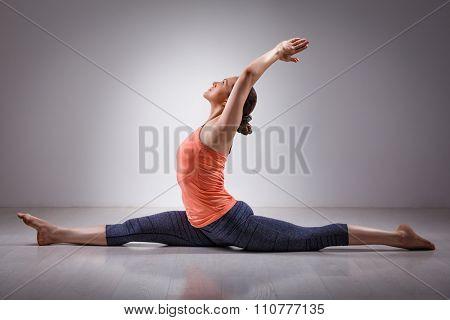 Sporty fit woman doing Hatha yoga asana Hanumanasana  (splits) - monkey pose