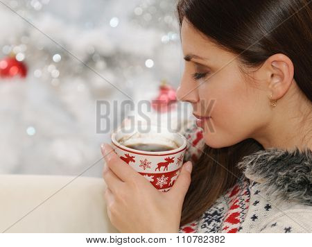 Clouse Up Shot Of An Attractive Young Woman Enjoying Hot Drink On Christmas Tree Background