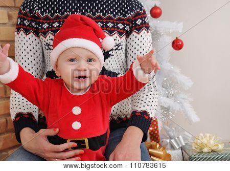Happy Cute Little Baby Boy In Santa Suit Sitting On Mother's Knees On Christmas Tree Background