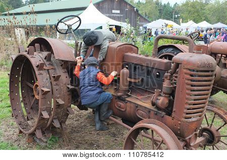 Children Playing On Old Farm Tractor