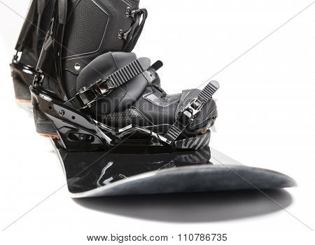 Black snowboard with bindings and boots attached on white background