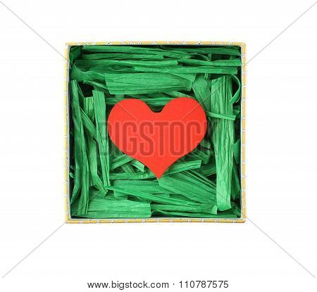 Red painted wooden heart enclosed with green paper raffia strips in paper box