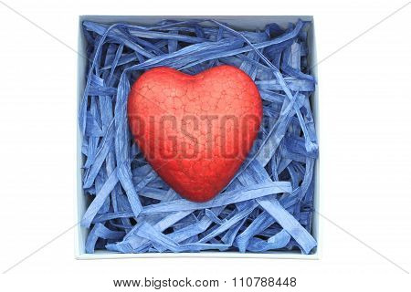 Red painted polyfoam heart enclosed with blue paper raffia strips in light blue box