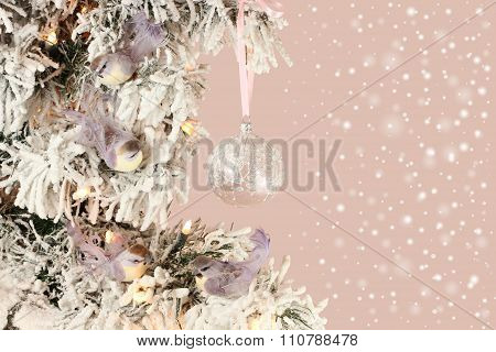 Decoration on Christmas tree - light violet birds and glassy ball on snowy spruce