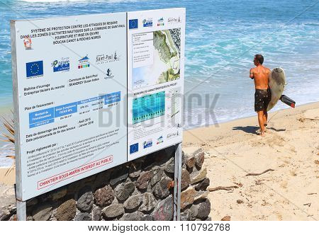 SAINT-PAUL, REUNION ISLAND, FRANCE - NOVEMBER 11, 2015: Wounded one hand surfer with damaged surfboard after shark attack standing near notice board with information about new anti shark steel net.