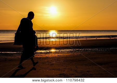 Silhouette Of Monk Walk On The Beach , Huahin , Thailand