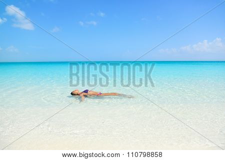 Woman swimming in ocean relaxing enjoying the sun bathing in peaceful blue water. Sexy female adult floating meditating in the sea.
