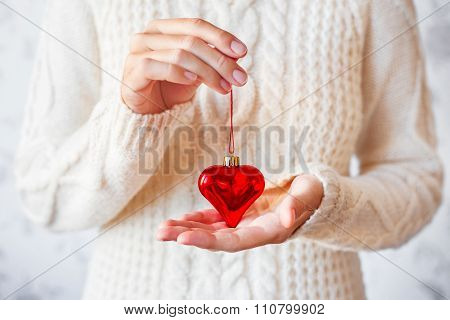 Woman In White Knitted Sweater Holding A Christmas Decoration - Bright Red Heart.