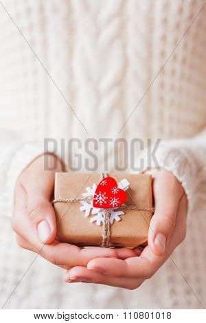 Woman In Knitted Sweater Holding A Present. Gift Is Packed In Craft Paper With Snowflake and Heart.