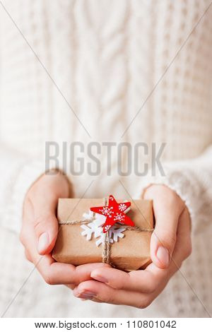 Woman In Knitted Sweater Holding A Present. Gift Is Packed In Craft Paper With Snowflake and Star