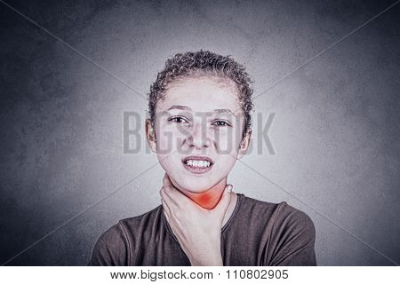 Little girl with sore throat touching her neck