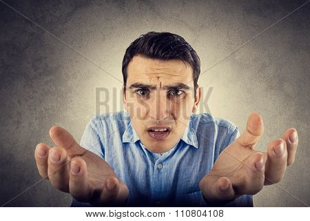 Undecided young student man isolated over grey background.Doubt facial expression