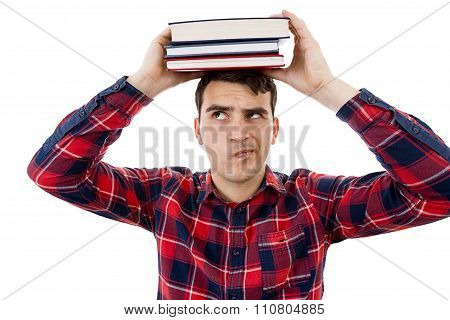 Thinking Young man student holding a stack of books on head