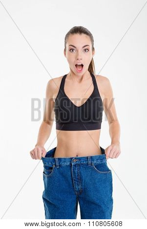 Shocked slim fitness girl in old jeans that became too big isolated over white background
