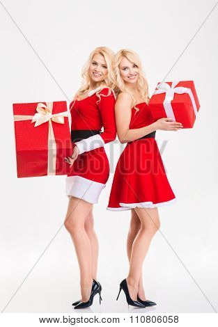 Full length of two smiling beautiful sisters twins in santa claus costumes  holding big gifts over white background