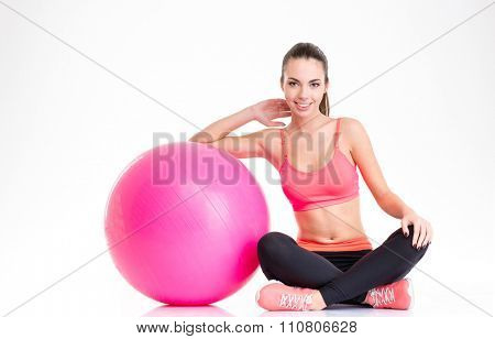 Beautiful happy fitness girl in tracksuit sitting and posing with pink fitball isolated over white background