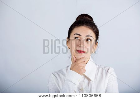 Young thinking woman looking up sideways