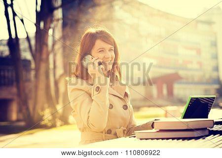 Smiling young woman student talking on mobile phone