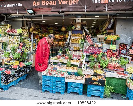 Paris Shopkeeper Examines His Vegetables At Fruit Stand