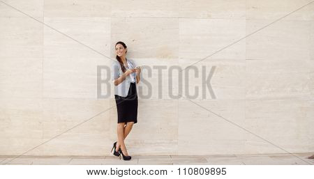Stylish businesswoman standing against a neutral cream colored wall holding her mobile phone and looking back over her shoulder  full length with bilateral copyspace